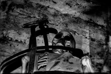 """Il mio corpo ha iniziato a rigenerarsi da solo. Seppur con fatica riesco ad esplorare il luogo in cui mi trovo. Alzo lo sguardo e la mia attenzione è attratta da decine di scheletri umani appesi al soffitto. Una volta si usava dire """"avere uno scheletro nell'armadio"""", ma qui non si scherza… Dove mi trovo?"""